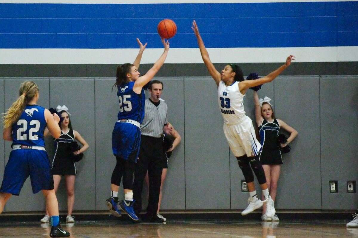 Friendswood's Hannah Bruce (25) tries to put up a shot over Clear Springs' Sierra Cheatham (33) Friday in a District 24-6A girls' basketball game.