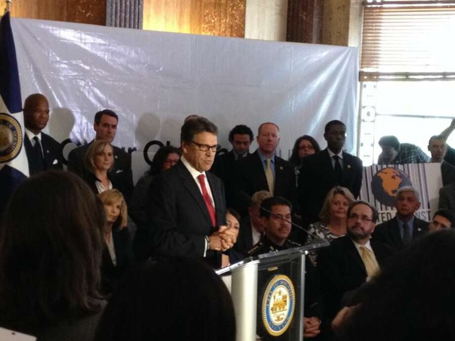 Gov. Rick Perry speaks to the media, announcing the state partnership to fight human trafficking between agencies. Photo: Alex Endress