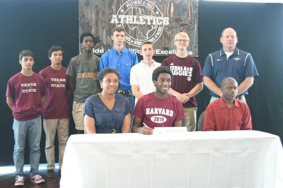 Kingwood track's Myles Marshall signs to run at Harvard on Friday, May 8, 2015, surrounded by teammates, who also signed. Back row, from left to right, Zach Alam (Texas State), Daniel Giannavola (Texas State), Charles Mills (University of Texas), Jacob Moore (Odessa College), Cameron Reagan (Texas Lutheran) and DeWitt Thomas (Texas A&M), Tate Symons (Kingwood Track Head Coach).