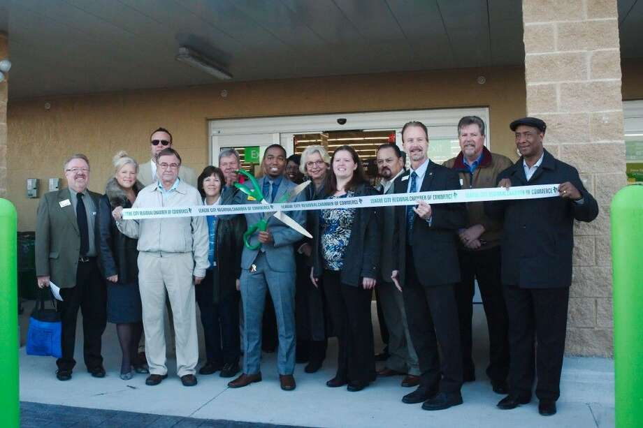 League City Mayor Timothy Paulissen, right center, joins Walmart Neighborhood Market Store Manager Zachary Morris as he prepare to cut the ribbon to open a new store in League City, Wednesday, Jan. 13.