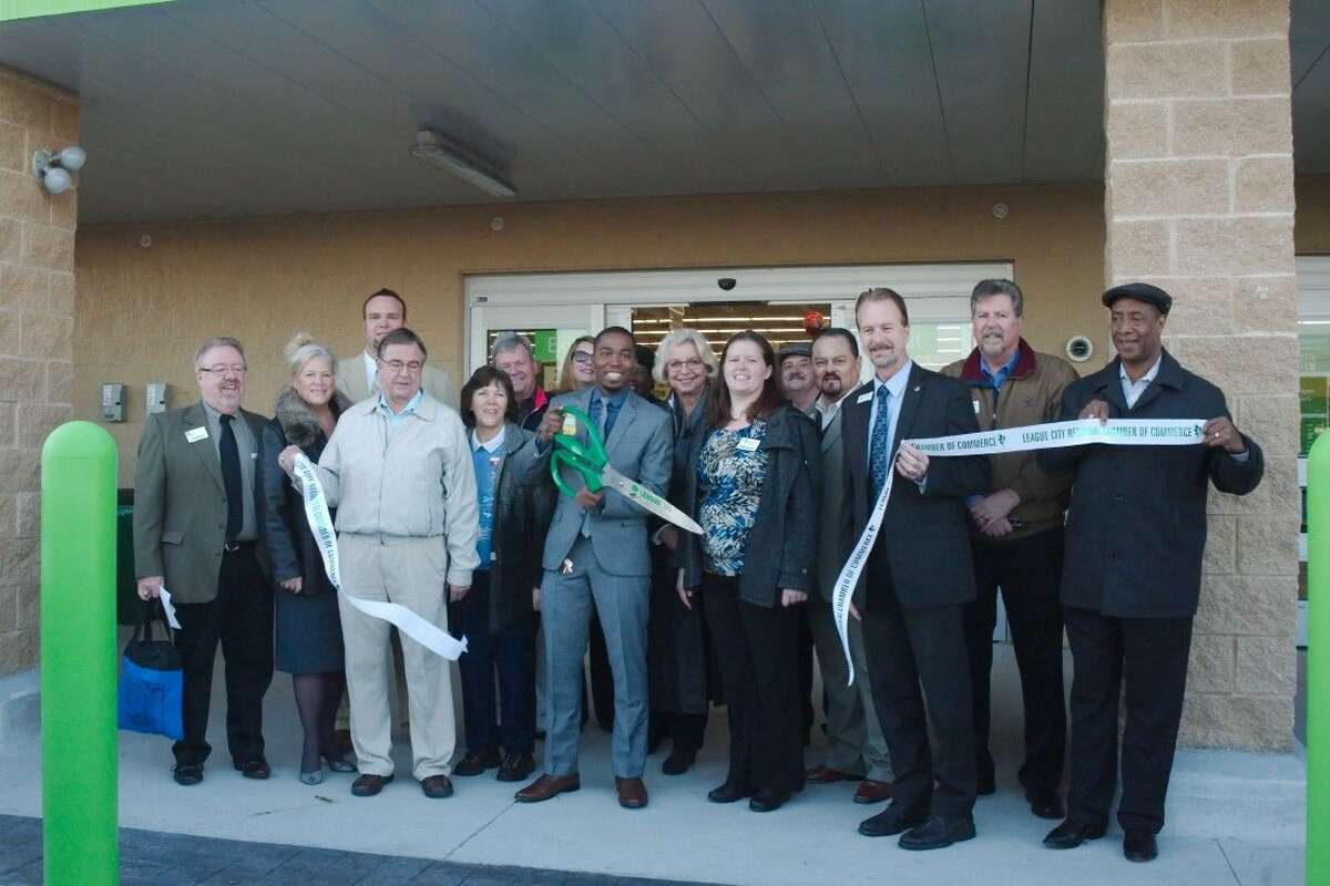 League City Mayor Timothy Paulissen, right center, joins Walmart Neighborhood Market Store Manager Zachary Morris as he cuts the ribbon to open a new store in League City, Wednesday, Jan. 13.
