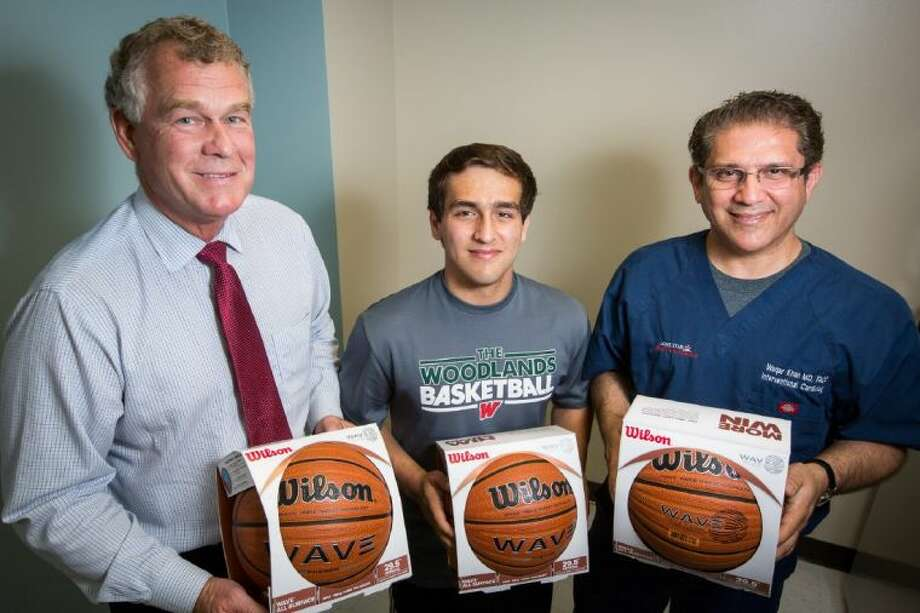 Omar Khan, head of Hungry for Hoops, center, is pictured with his father Waqar Khan, right, and Ronny Peacock, Tomball ISD Athletic Director, left, on Thursday, May 5, 2014, at Waqar Khan's office in Tomball. Omar raised money through the charity, Hungry for Hoops, to buy hundreds of basketballs for Tomball ISD elementary school students. Photo: Michael Minasi