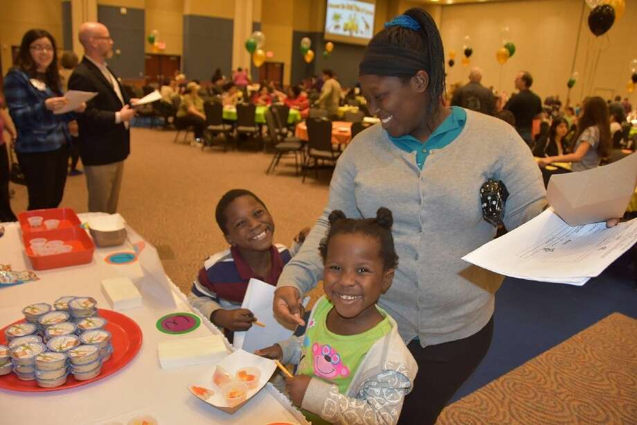 Family members sample fruits and other snack offerings at the Annual Food Tasting event at the Berry Center on Jan. 14.