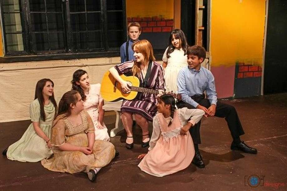 "Star vocalist Sarah Hames as Maria is surrounded by stars-of-the-future the von Trapp children in ""Sound of Music"" at Pasadena Little Theater. Pictured, (on floor L to R) Lauren Huchton, Haylee Wuensche, Julie Miles, Aimee Ramos (on bench) Sarah Hames, Phillip Barrero (Back row) Trace Muse, Madeline Leal."