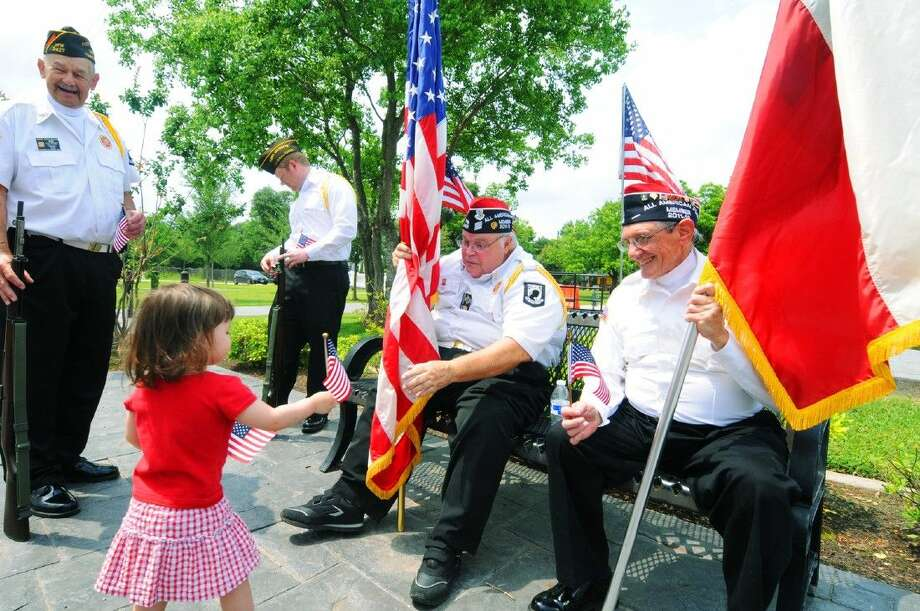 Army veteran Mike Lavender reaches out to a little flag girl for her United States flag. Lavender and the rest of the veteran color guard members were on hand for National Day of Prayer ceremonies in Tomball. Photo: Tony Gaines