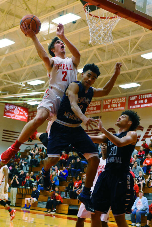 Tomball senior guard Cullin Johnson skies for an offensive rebound and putback Friday, January 15, 2016 at Tomball High School against Tomball Memorial. Johnson was a dynamo, catalyzing the Cougars' 54-41 victory over the rival Wildcats. Photo: Tony Gaines