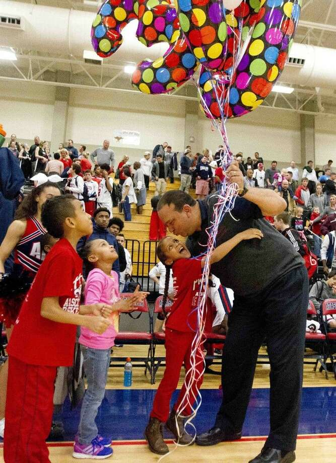 Atascocita head coach David Martinez gets a hug from his kids after winning his 300th career game Tuesday, Jan. 5, 2015. To purchase this photo and others like it, go to HCNpics.com. Photo: Jason Fochtman