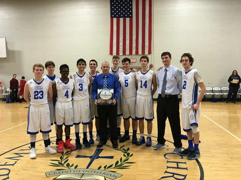 Following his 200th career coaching victory the Northeast Christian Academy boys basketball team surrounded Matt McLeod to celebrate the milestone victory.