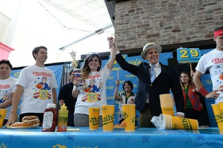 Nathan's Female Winner Crystin Pactor secures her trip to Coney Island with her win at the Nathan's Famous Hot Dog Eating Qualifier at Memorial City Mall. Pictured, l-r, Female winner Crystin Pactor and Major League Eating Chair George Shea. Photo: DANIELORTIZPHOTOGRAPHY