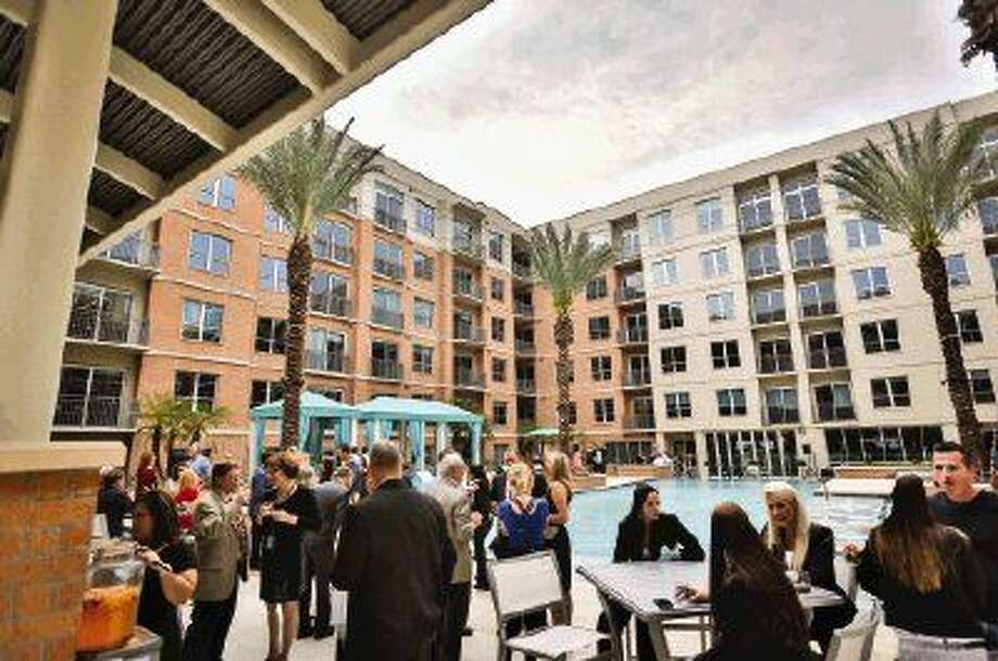 Invitees of the grand opening of One Lakes Edge mingle by the pool on the third floor of the complex on Friday, May 8 at Hughes Landing. Photo: Michael Minasi