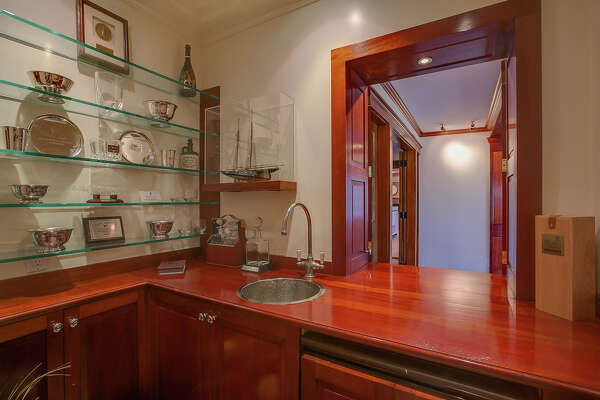 This house has a wet bar room, ideal for entertaining, with a hammered nickel sink, wood counters, cabinetry, a dishwasher, and a wall of glass shelving for storage of stemware.