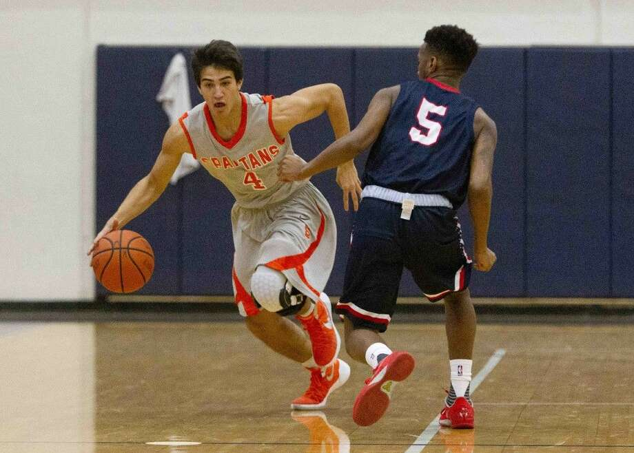 Seven Lakes point guard Diego Martinez drives the ball during the Insperity Holiday Classic, Dec. 28 at Kingwood High School. Martinez and the Spartans rallied for a 61-57 victory at Cinco Ranch on Jan. 8, ending the Cougars' 20-game district winning streak. Go to HCNpics.com to purchase this image and view more photos from the tournament. Photo: Jason Fochtman