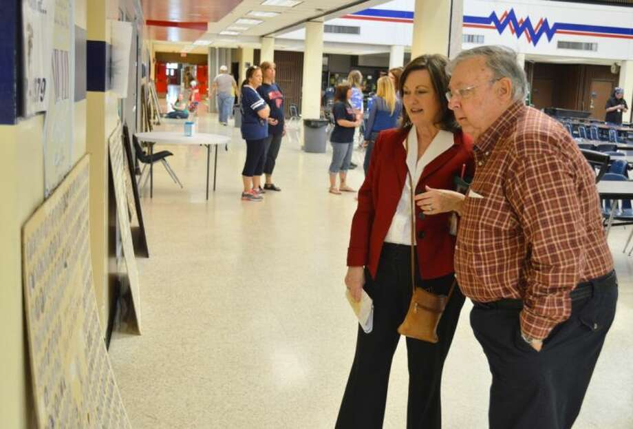 Clear Lake HS Alumni, Mary Lou Johnson (currently CCISD Coordinator of Visual and Performing Arts) & Ralph Parr, former Clear Lake High School Assistant Principal look at senior class photos from years past.