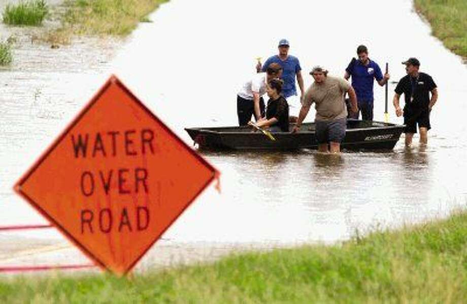 Owners and employees of the the Dutch Lions FC Complex and Bel-Ray Action Sports Park come back toward the F.M. 1488 after taking a boat they purchased to observer the damage to the two complexes caused by flooding Wednesday.