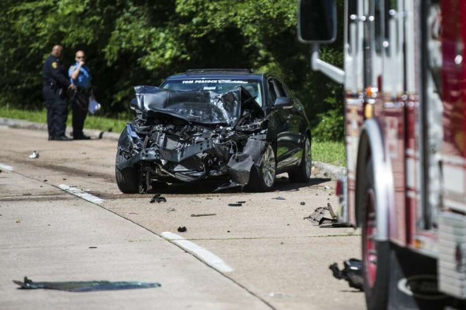 A Cadillac waits to be removed from the road after a two-car accident that left one woman dead June 11, 2014, on Kingwood Drive near Kingwood High School. Photo: ANDREW BUCKLEY