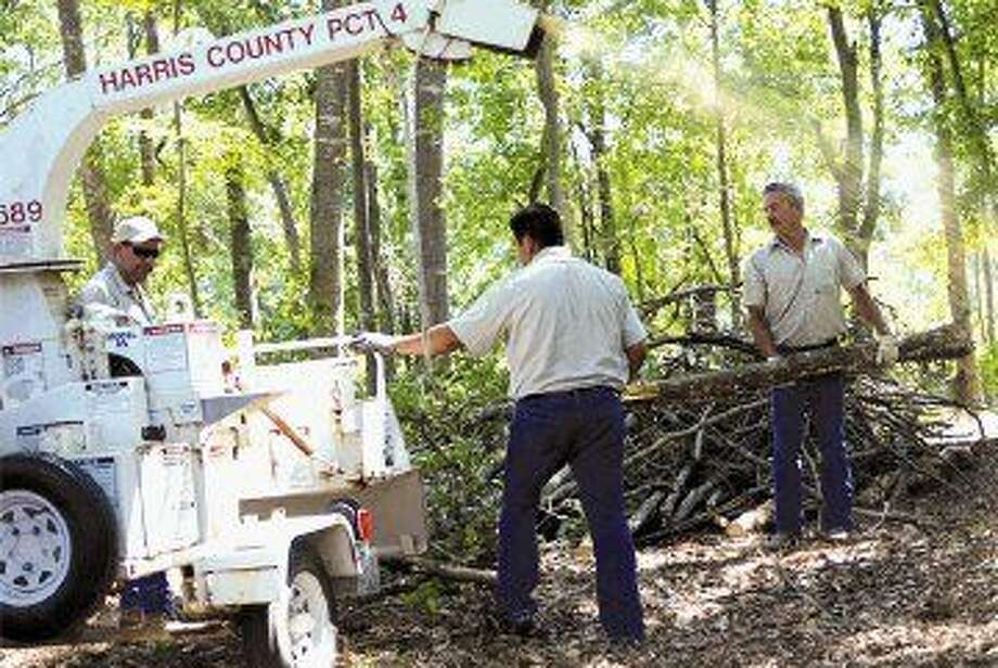 Precinct 4 employees place fallen limbs in a wood chipper to clear a trail.