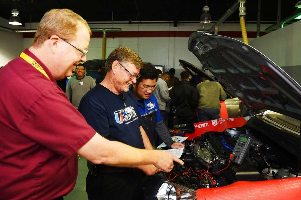 Benny Williams (middle), a 55-year-old student at UTI, listens to instructor Martin Keefer and advance student Phu Le in metering and measuring car voltage.