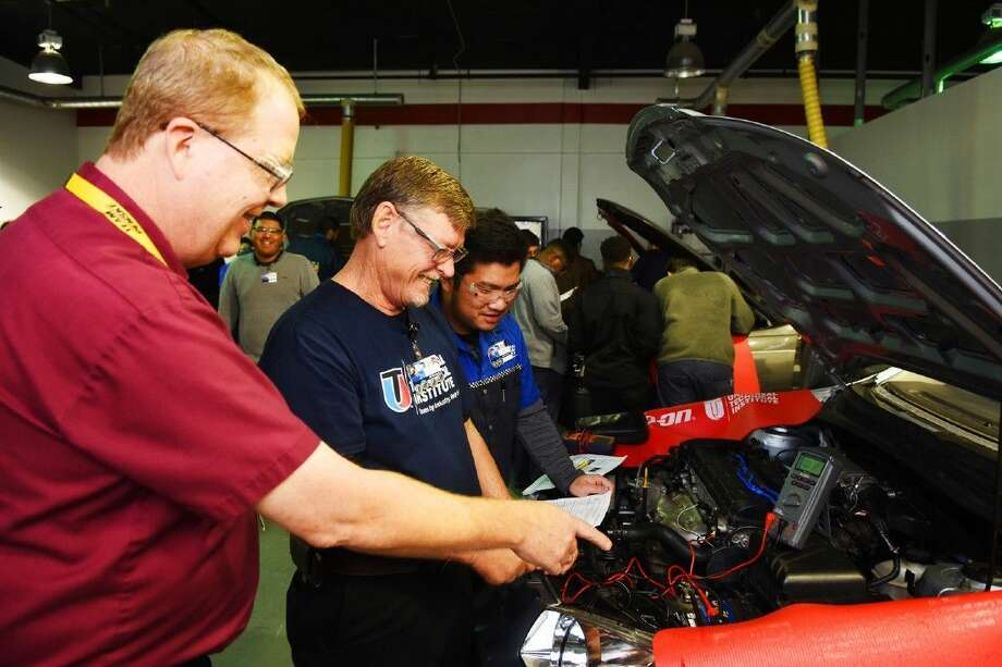 Benny Williams (middle), a 55-year-old student at UTI, listens to instructor Martin Keefer and advance student Phu Le in metering and measuring car voltage. Photo: Tony Gaines