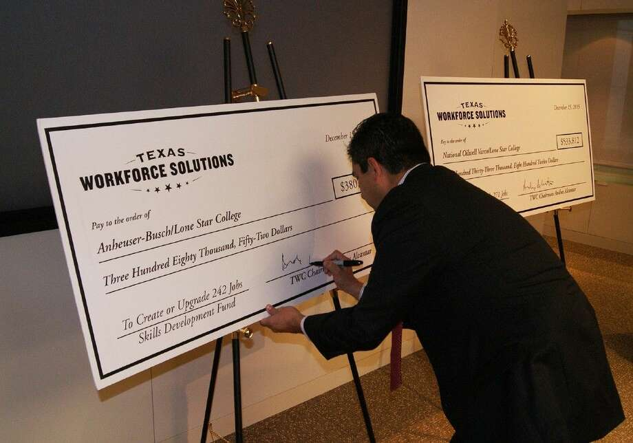 TWC Chairman Andres Alcantar signs checks for the $913,865 Skills Development Fund grants given to Lone Star College by Texas Workforce Solutions to help train current and new employees at National Oilwell Varco and Anheuser-Busch. Photo: Submitted