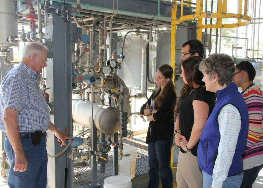 """College of the Mainland professor Pete Rygaard explains the workings of the glycol separation unit, used in local industry, to Texas Commission on Environmental Quality employees. The employees """"became process technicians"""" during one of COM¹s customized trainings to gain a greater understanding when inspecting plants and determining causes of incidents. Photo: Courtesy College Of The Mainland"""