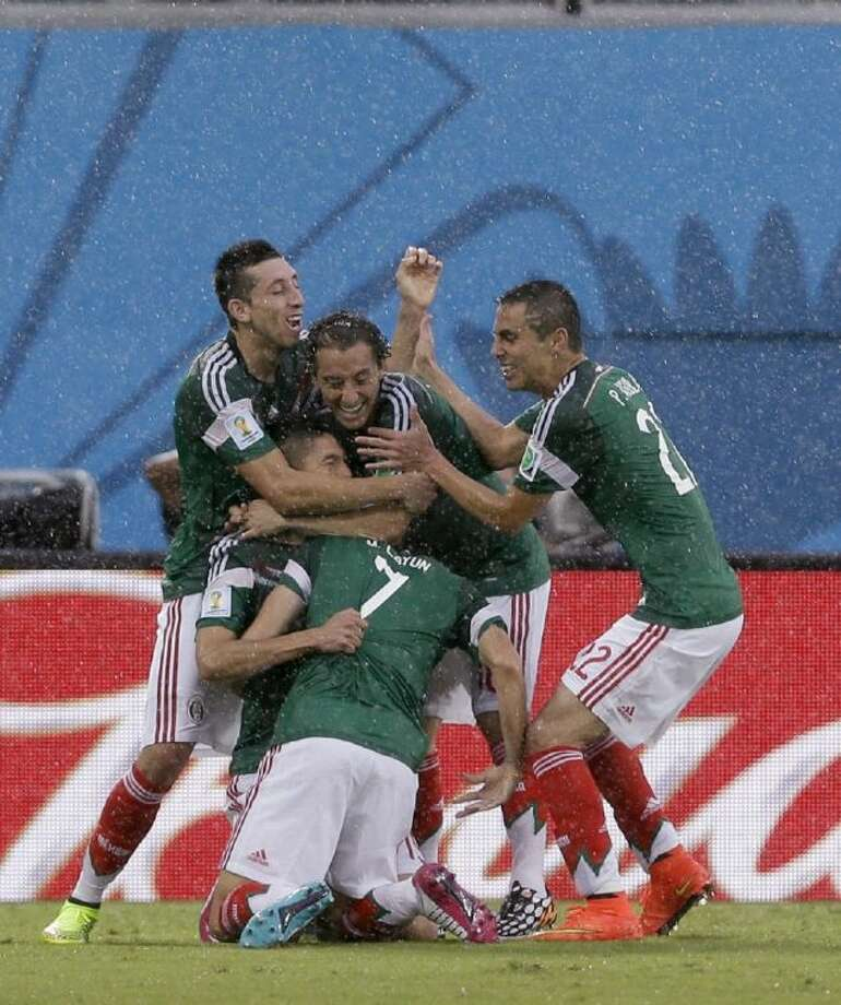 Mexico's Oribe Peralta celebrates with teammates after scoring the opening goal during a Group A World Cup match against Cameroon on Friday at Arena das Dunas in Natal, Brazil.