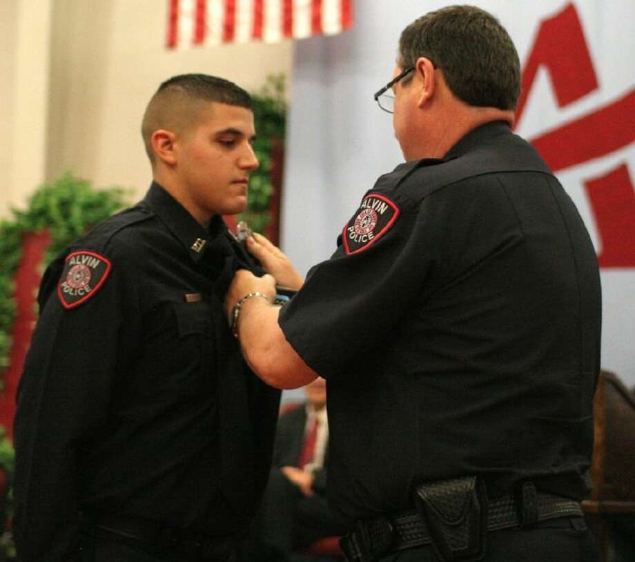 Alvin Police Chief Robert E. Lee, right, pins a police badge on Law Enforcement Academy graduate Diego Olivarez during a graduation ceremony on May 29.