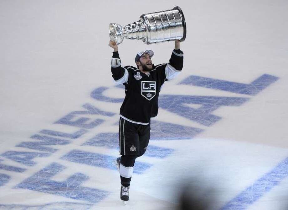 Defenseman Alec Martinez carries the Stanley Cup after the Los Angeles Kings defeated the New York Rangers 3-2 in double overtime in Game 5 of the Stanley Cup finals Friday in Los Angeles.