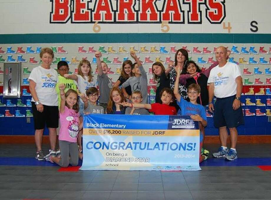 Black Elementary School students and P.E. teachers Mary Miller and Kurt Anselmi celebrate raising more than $16,200 for the Juvenile Diabetes Research Foundation (JDRF) during a presentation at the school last month.