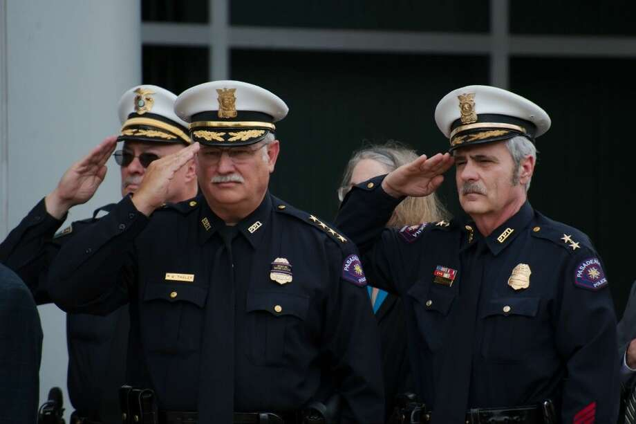 Pasadena Chief of Police Mike Thaler and Assistant Chief Michael Jackson stand at attention during the singing of the National Anthem during the Annual Police Officer Memorial Service Thursday, May 14.