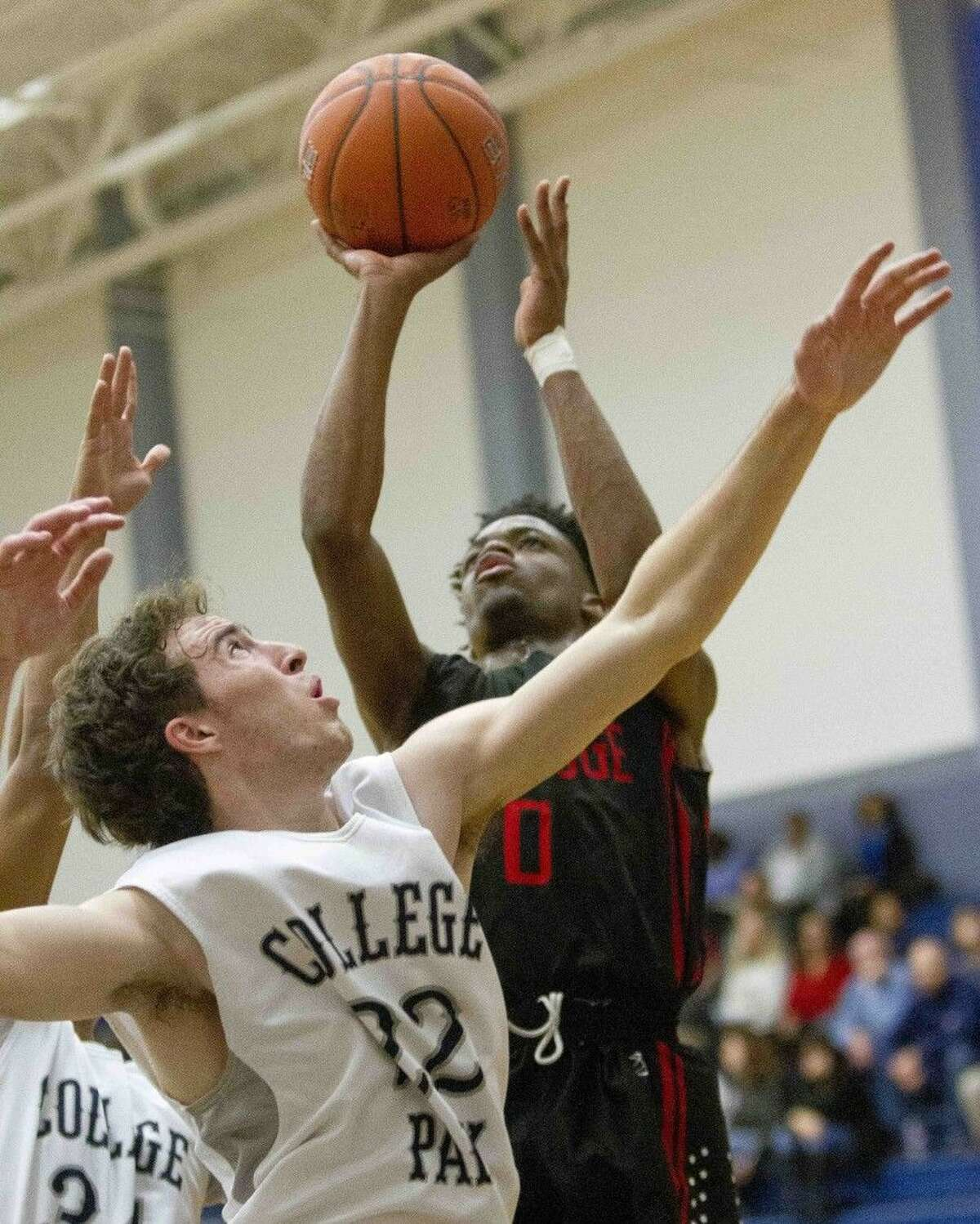 Oak Ridge guard Darius Love goes up for a shot as College Park forward Dax DeBoer defends during a basketball game Tuesday. Go to HCNpics.com to purchase this photo, and others like it.