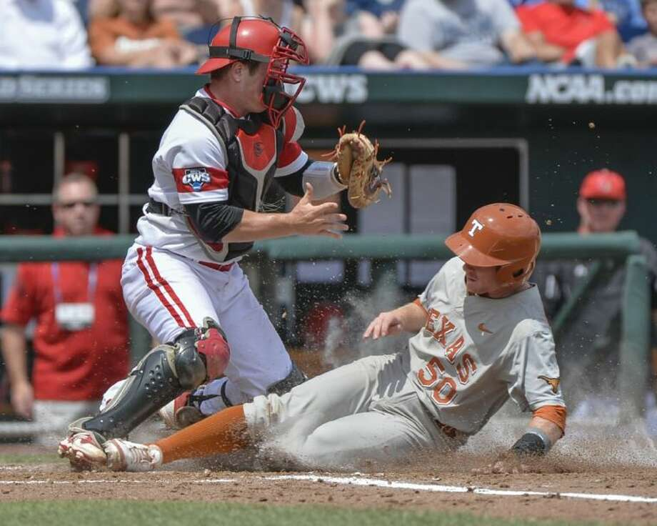 Texas base runner Zane Gurwitz, right, scores as Louisville catcher Kyle Gibson takes a late throw. The Longhorns beat Louisville 4-1 to stay alive in the CWS.