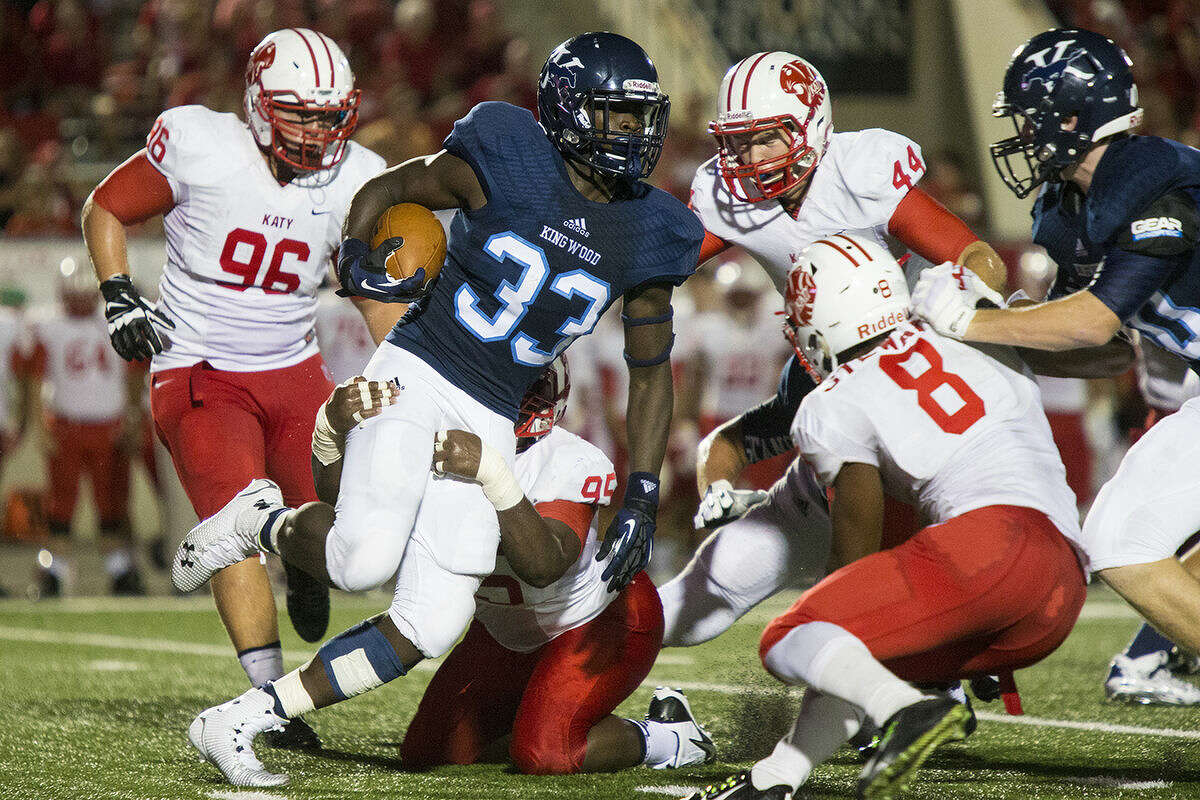Mustangs running back Sewo Olonilua attempts to break through the defense during Kingwood's matchup against Katy on Aug. 29, 2014, at Turner Stadium in Humble.