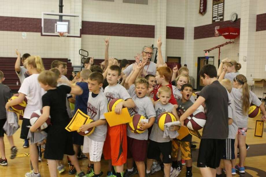 At the end of the last day of basketball camp, Coach Greg Scharer, Coach Karen Suggs and the children gathered together for one final cheer. Photo: JACOB MCADAMS