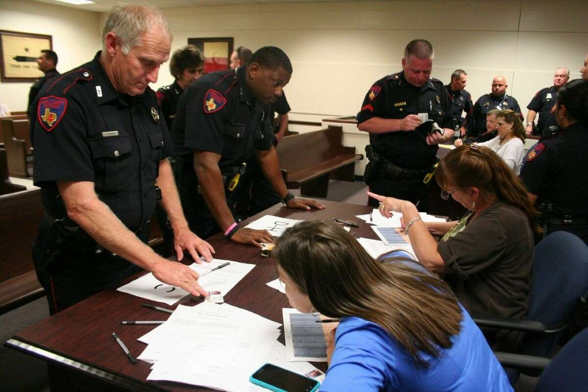 Law enforcement officers with Harris County Precinct 4 Constable's Office receive their new paperwork and identification badges after being sworn in May 26, 2015.