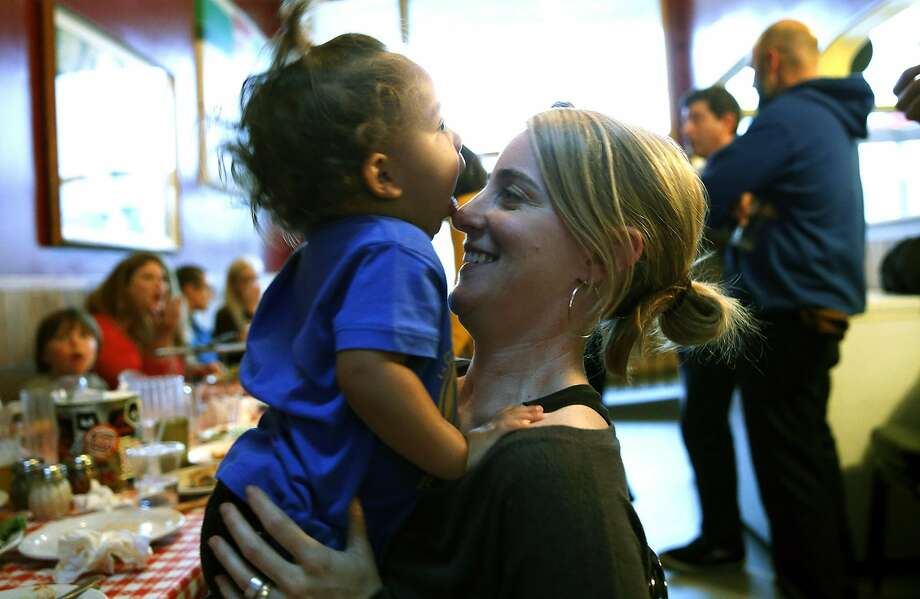 During a pizza party celebrating two sets of married teachers acquiring homes in San Francisco, teacher Bridget Early holds her daughter, Ellie, 1. Photo: Scott Strazzante, The Chronicle
