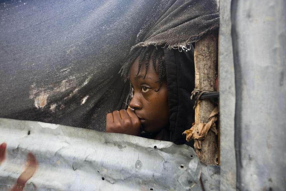A girl watches as authorities arrive to evacuate people from her house in Tabarre, Haiti. Photo: Dieu Nalio Chery, Associated Press