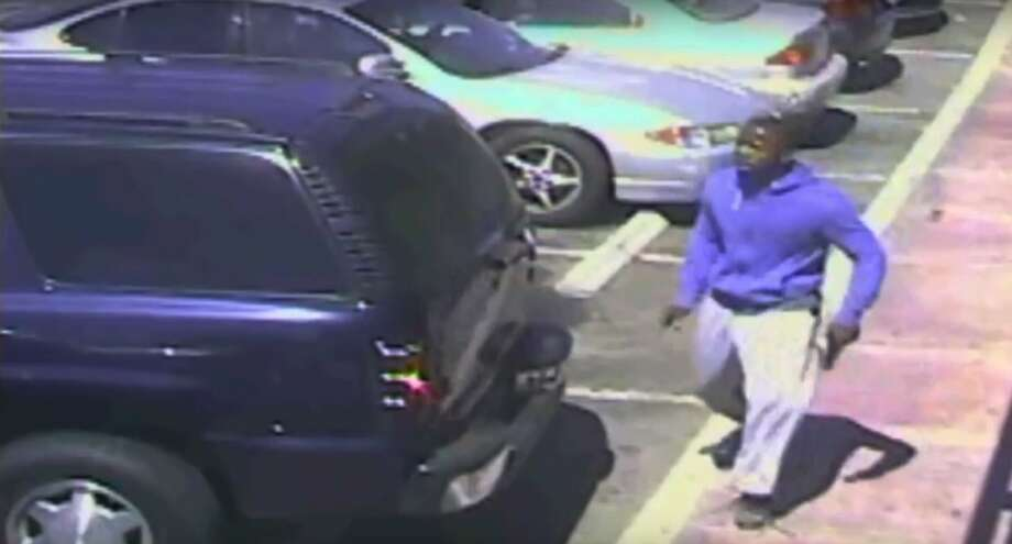 A security camera video shows a suspect holding what appears to be a gun in the moments before he was fatally shot by police. Photo: Associated Press