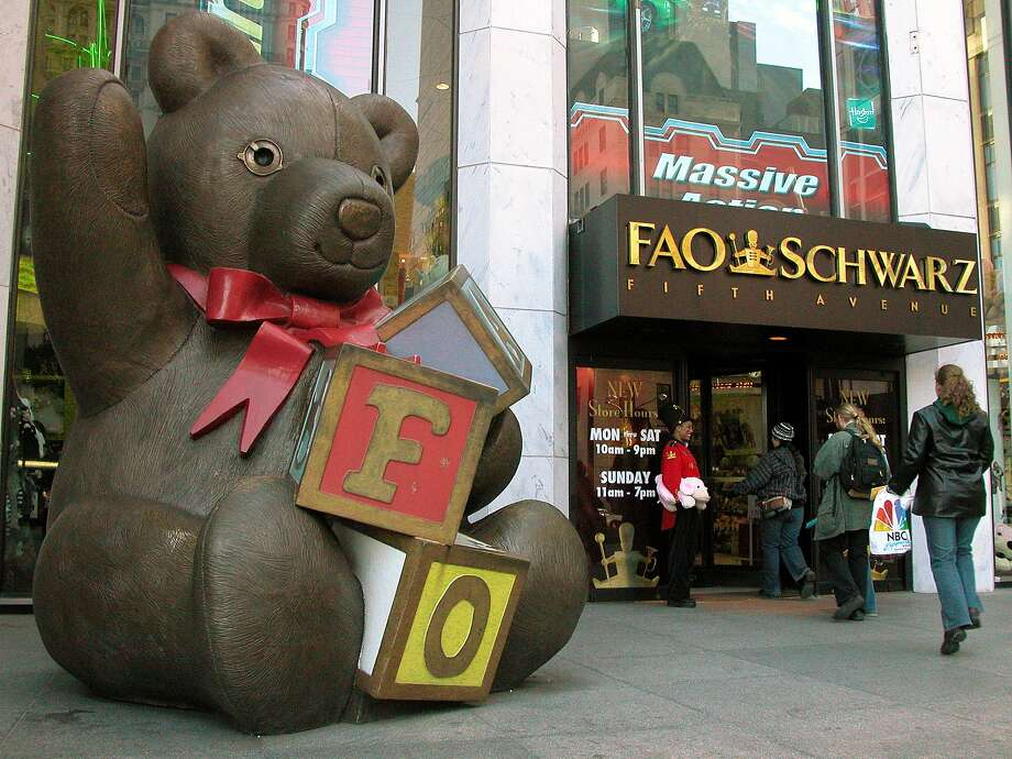 People pass a statue of a teddy bear and a doorman dressed as a toy sholdier as they enter the FAO Schwarz on Fifth Avenue in New York Monday, Nov. 10, 2003. Photo: RICH KARECKAS, AP
