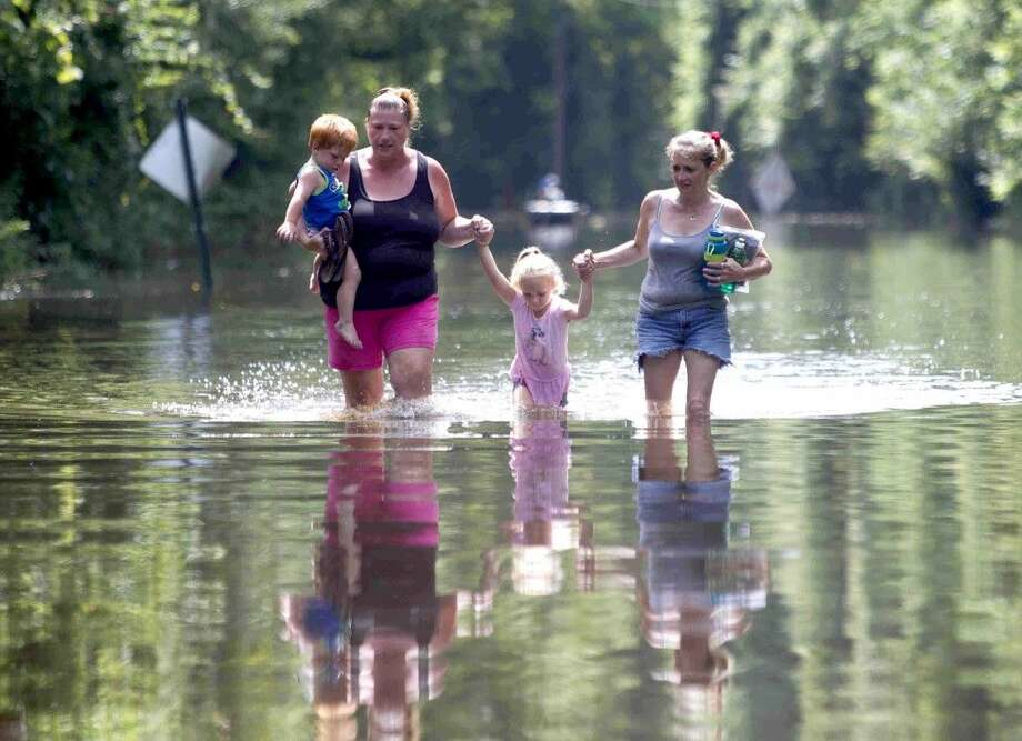 Residents of Knights Forest subdivision wade through knee deep water as they leave their homes in Hardin on May 28. Heavy rain, coupled with increased water released from the Lake Livingston Dam, has caused the Trinity River to flood several neighborhoods near the river four times in 2015. Photo: Jason Fochtman
