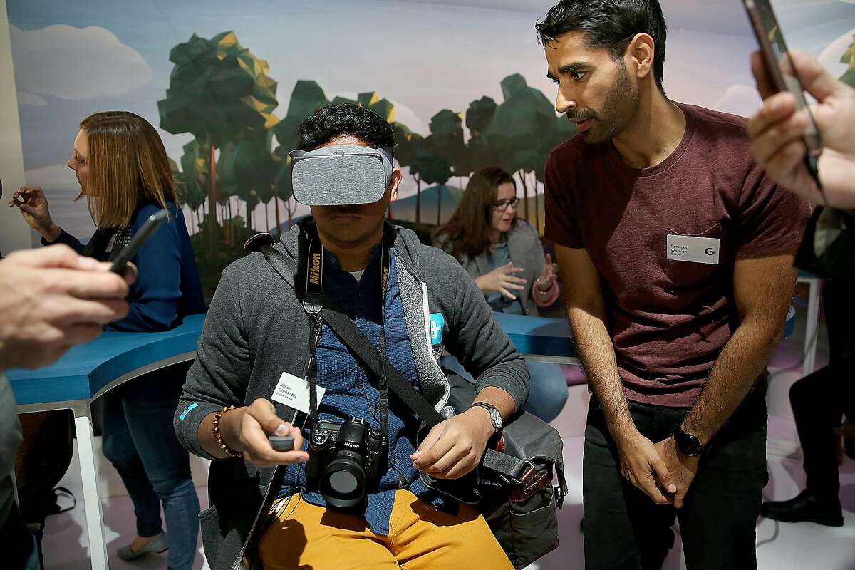 Julian Chokkattu (left) from digital Trends tries out 3D viewer with Google's Saneep Waraich (right) during a press conference at Fisherman's Wharf on Tuesday, October 4, 2016, in San Francisco, Calif.