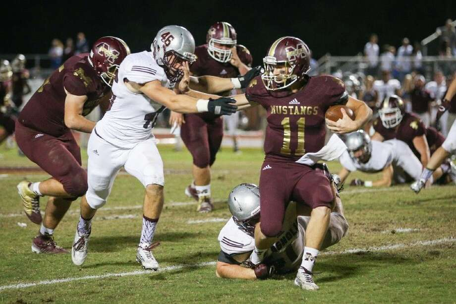 Magnolia West's Tyler Ferré is brought down by Magnolia defensive tackle Spencer Nigh, The Courier's Defensive MVP.