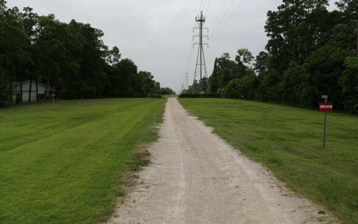 Looking north at a CenterPoint transmission corridor in West Houston. The corridor is fenced and gated to restrict access. There are no current plans for a trail in this corridor.