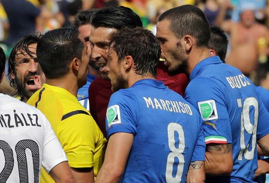 Italy goalkeeper Gianluigi Buffon, in red, argues with referee Marco Rodriguez after he sent off Italy's Claudio Marchisio during the Italians' Group D World Cup match against Uruguay on Tuesday at Arena das Dunas in Natal, Brazil.