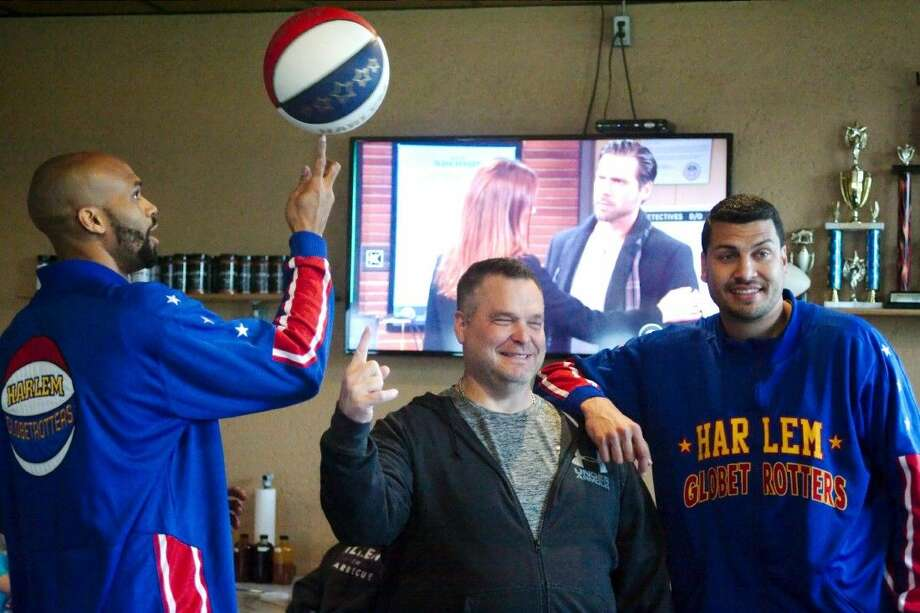 "Killen's Barbecue owner Ronnie Killen learns a few tricks from Harlem Globetrotters ""Hawk"" Thomas and ""El Gato"" Melendez as the Globetrotters visit the restaurant Tuesday, Jan. 26. Photo: Kirk Sides"