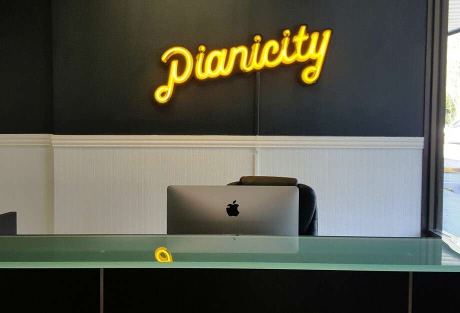 A neon sign is mounted on the black wall behind the receptionist's desk at Pianicity in Kingwood.