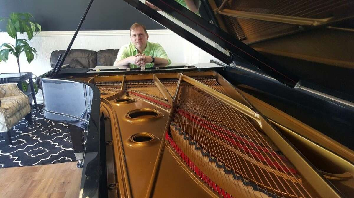 Pianist and composer Matthew Mason poses at his piano which used to belong to Richard Palmer, chief aeronautical engineer and close colleague of Howard Hughes.