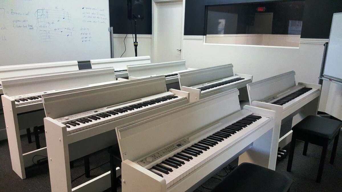 Rows of Korg digital pianos are set up for group lessons in one of Pianicity's classrooms.