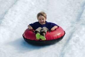 Colt Schoeffler rides a tube down the HEB snow hill at the City of Pearland Winterfest Saturday, Jan. 30.