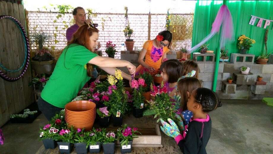 P.J. Whitehouse, director of Heights Plant Farm Summer Camp, helps campers with grooming plants.