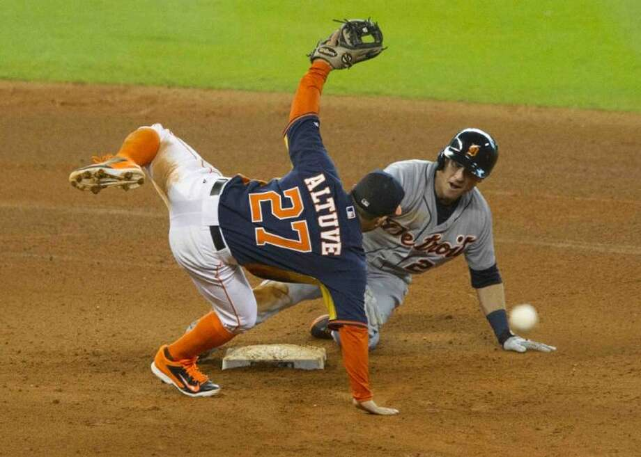 Astros second baseman Jose Altuve leaps over the Tigers' Andrew Romine to turn a double play in the Astros' 6-4 victory. Go to HCNpics.com to view more photos from the game.